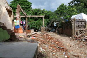 A girl in Oaxaca stands beside her destroyed home