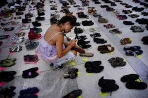 A woman places a shoe in memory of those died