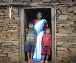 Manju poses in front of her house with her 2 sons