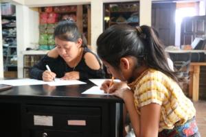 Dolores y Julisa escribiendo palabras en Tz'utujil
