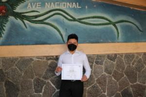 Misael displaying his diploma