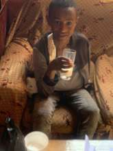 Alemu in his home drinking milk and resting