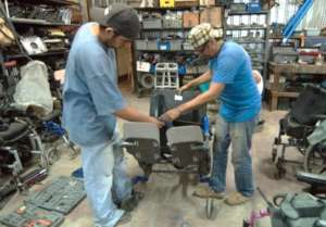 2 deaf young people work on wheel chair adaptation