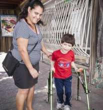 Mother with child receiving specialized Walker