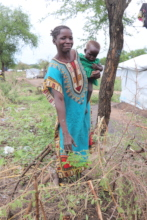 Fatima* and her child with a moringa seedling