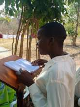A girl guiding each on how to read at KIFA