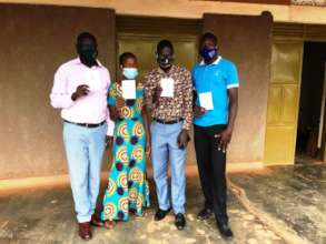Staff take photos with cards for COVID-19 vaccine