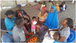 Women with children in small group discussion.