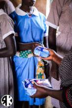 Girls receiving their own AFRIpads Kit