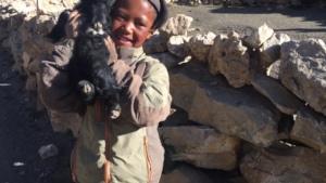 Tsharka student holding baby goat