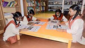 Girl students in the library reading newspapers