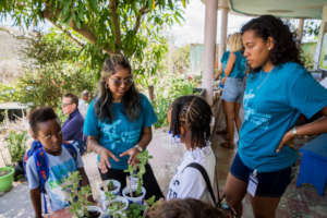 Student volunteers teach kids about plants.