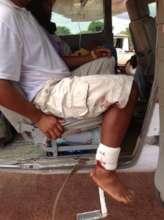 An injured man awaits departure.