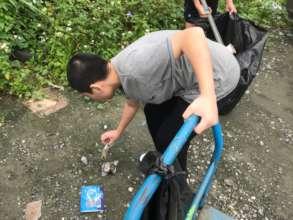 A Boy bend down to pick up trash