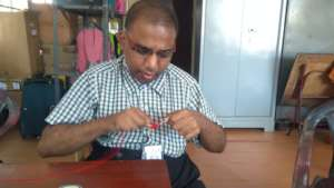 Naveen engrossed in making a colourful pompom