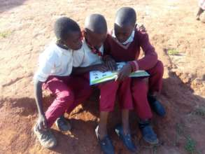 Pupils helping each other read outside the school