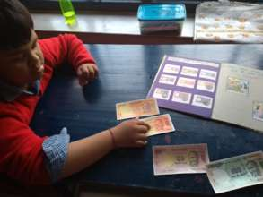 Child identifying 20 Rupee note using TLMs