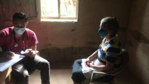 Doctor seeing patient in village: mobile clinic