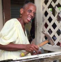 A joyful homeowner hammers the last recovery nail