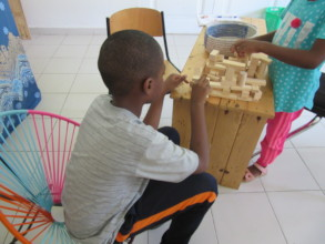 A student and his sister play with blocks
