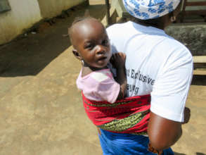 A community health worker carries her baby