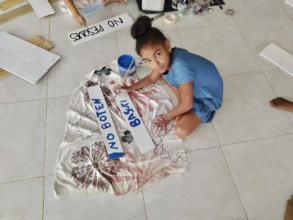 Local girl painting sign with environmental note