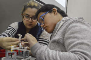 Two young deaf women learning robotics