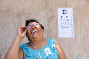 Woman smiles as she receives new glasses