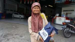 Local woman picks up food aid from ACT