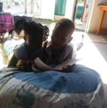 An older child reading to a younger child
