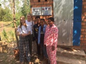 Family proudly displaying new brick latrine