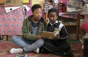 Youth volunteer reading to a child