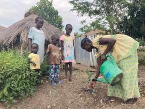 Children watch their mother plant a jackfruit tree