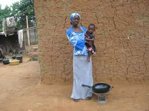 Afia with her daughter, coal pot and frying pan.