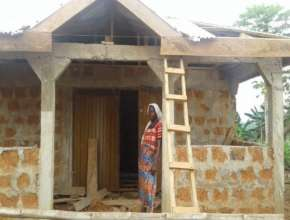 Saudatu with her store during construction