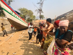 Local women help pull the boat to the water