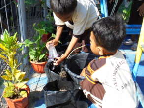 Students of rebuilt school learning to plant seeds