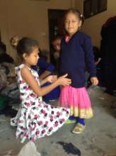 sister helps her sibling try a new school sweater