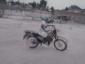 A lady practicing how to ride a motorcycle