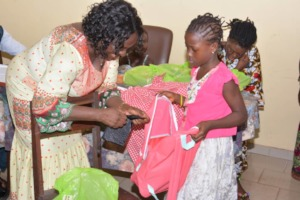 Child receiving backpack and school supplies.