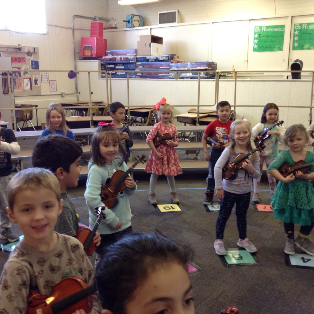 JOY is a kindergartener playing the violin.
