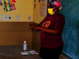 Nurse Domond instructs on COVID-19 hygiene.