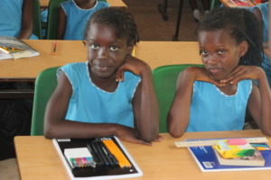 2 girls seated with school supplies