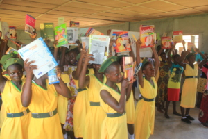 Girls holding the books we helped to provide