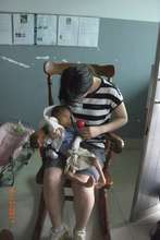 Seisen student comforts infant at City Orphanage