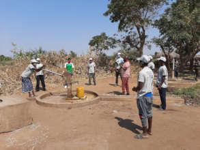 Trainees test a hand pump after assembling parts