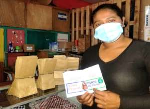 Mother shows stampted pasport for bags project.