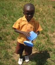 Kofi, a pupil, carrying his bowl.