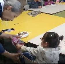 (Before pandemic) Little girl puts on her shoe