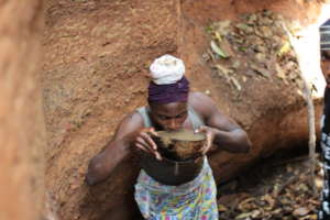 Zokotu woman drinking dirty water from the cave